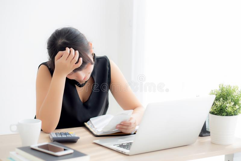Beautiful young asian woman calculating expenses household and writing notebook on desk. Girl checking bill and stress and note, female worry debt and tax stock photo
