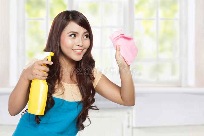 Beautiful young asian woman doing chores, holding sprayer and pi stock photography