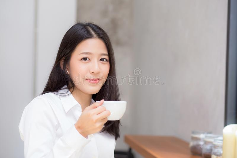 Beautiful young asian woman drinking coffee and smile in the morning at cafe stock images