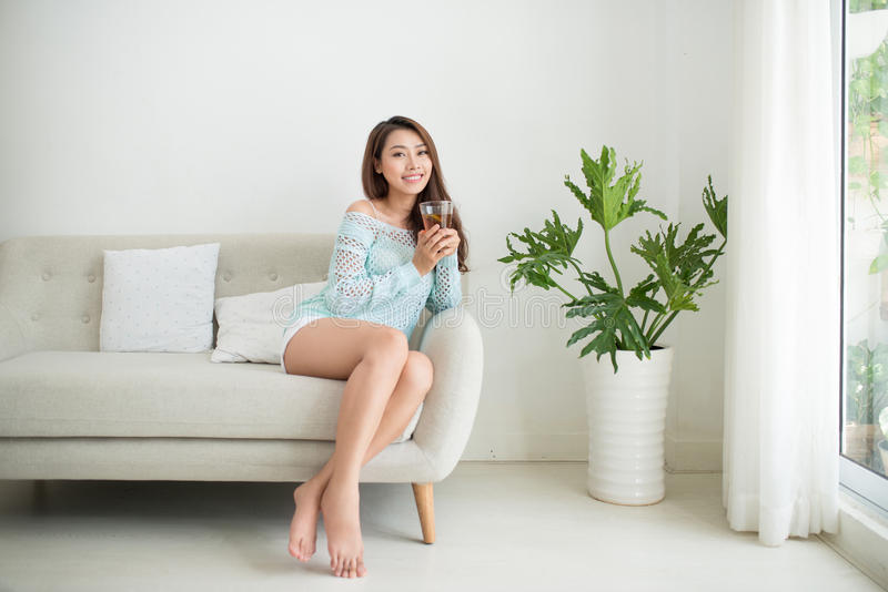 Beautiful young asian woman drinking her morning tea over a breakfast at home. royalty free stock image