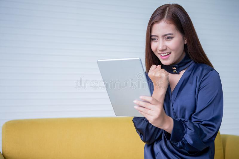 Beautiful young asian woman excited looking at digital tablet computer smiling girl with touch pad on yellow sofa stock images