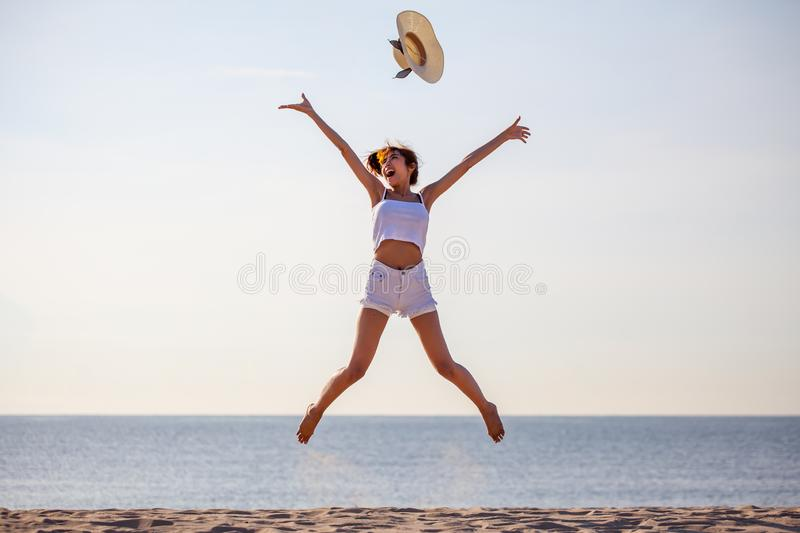 beautiful  young asian woman  excited throwing hats up on the air  at the sea beach . Happy girl enjoy  holidays vacation . stock image