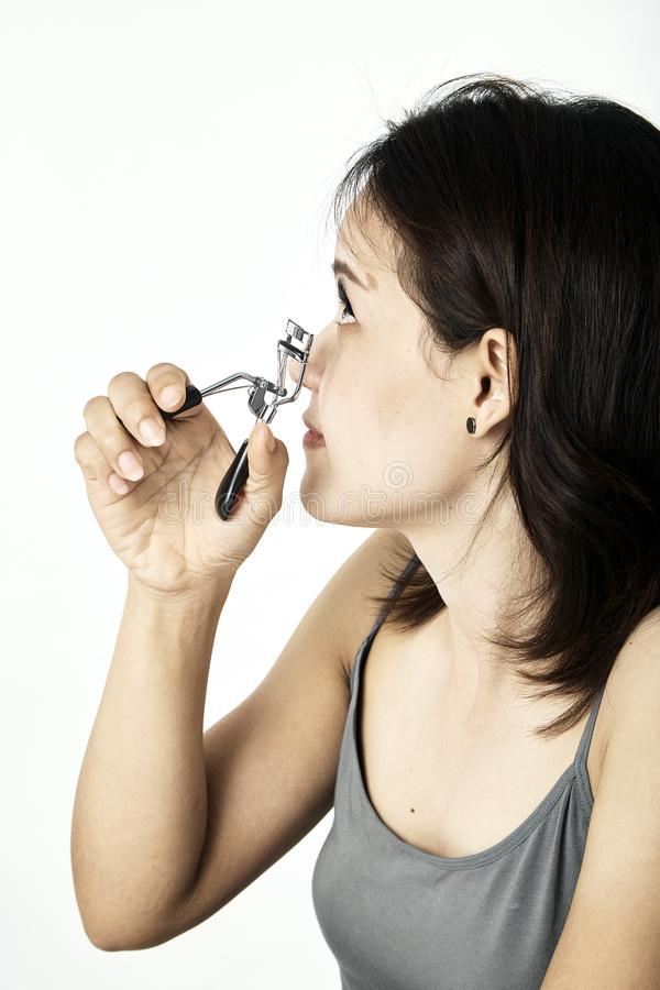 Young woman with eyelash curler on white stock photos