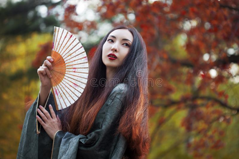 Beautiful young Asian woman with fan on background of red maple stock photo