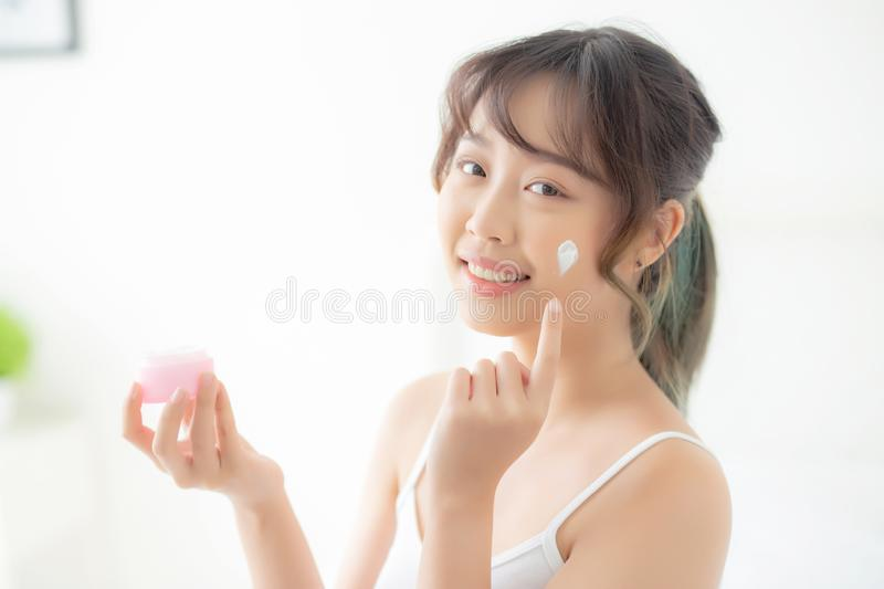 Beautiful young asian woman happy applying cream or lotion with moisturizer to skin face stock photo