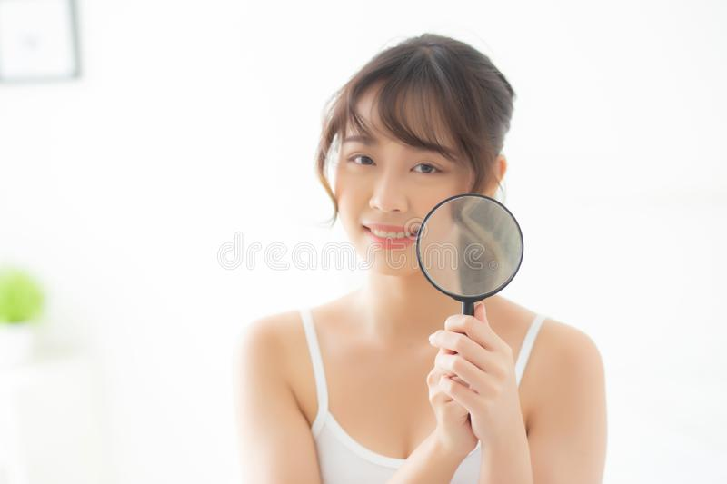 Beautiful young asian woman happy with magnifying skin of acne, beauty asia girl smiling check skincare of face. Female analyzing trouble, cosmetic and makeup stock image