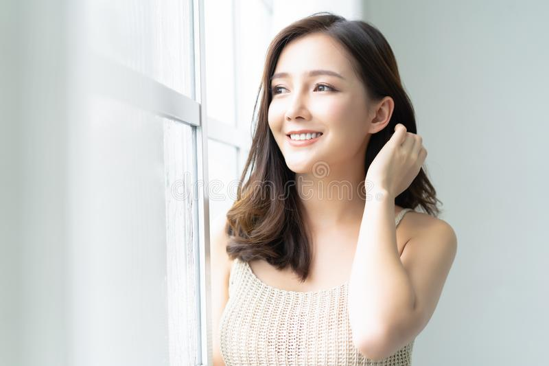 Beautiful young Asian woman leaning at the glass window and looking through window at her home. Morning. Good Mood.  Lifestyle and stock photo