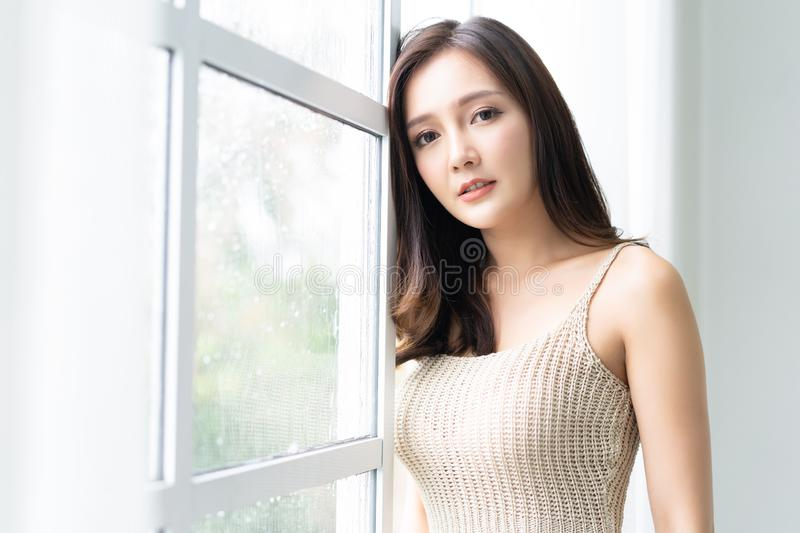 Beautiful young Asian woman leaning at the glass window with rain drops and looking at camera at her home. Morning. Mood. royalty free stock image