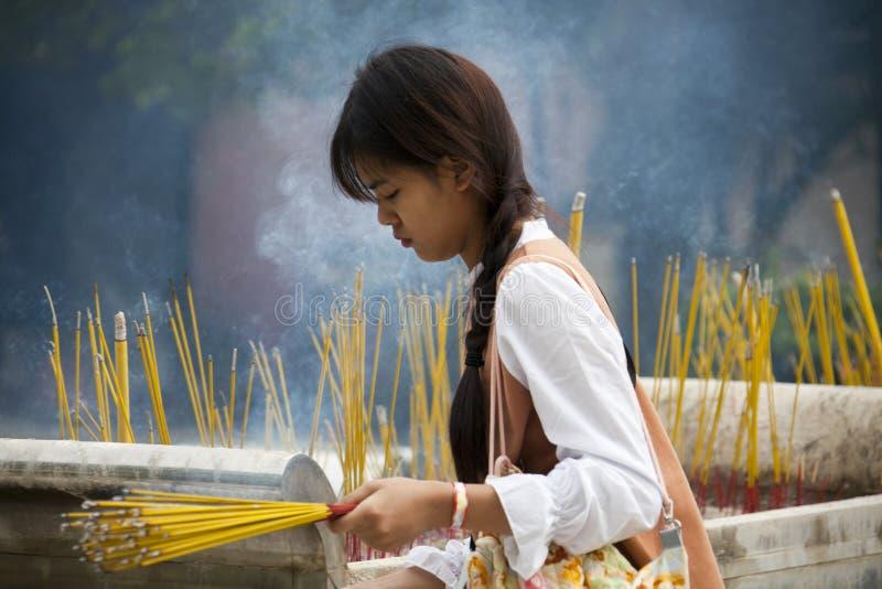 Beautiful young woman lighting incense sticks stock photos