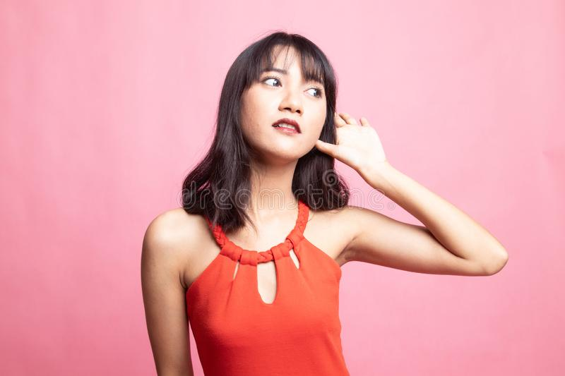 Beautiful young Asian woman listen to something. On pink background stock photos