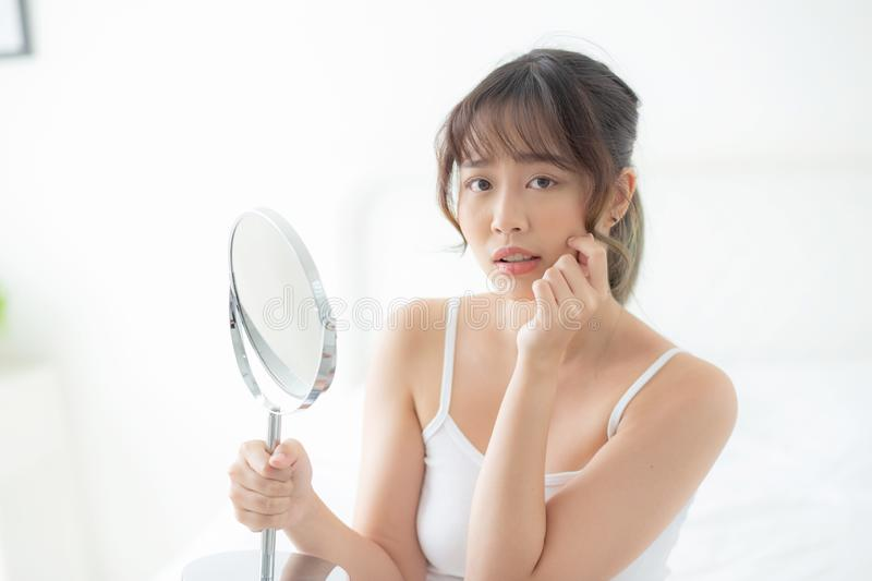 Beautiful young asian woman looking the mirror with acne problem at bedroom, trouble of beauty on face royalty free stock photos