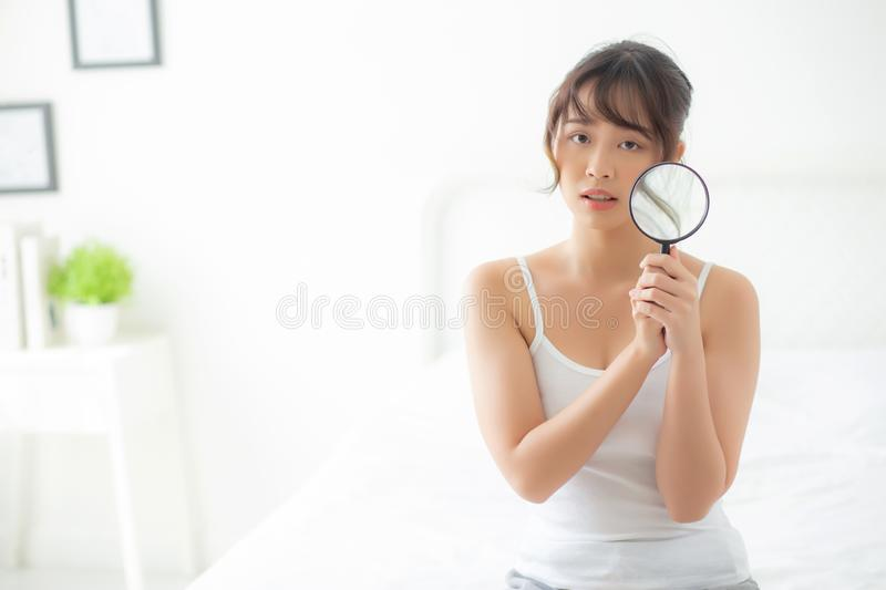 Beautiful young asian woman with magnifying of skin a problem of acne, beauty asia girl check skincare of face stock images