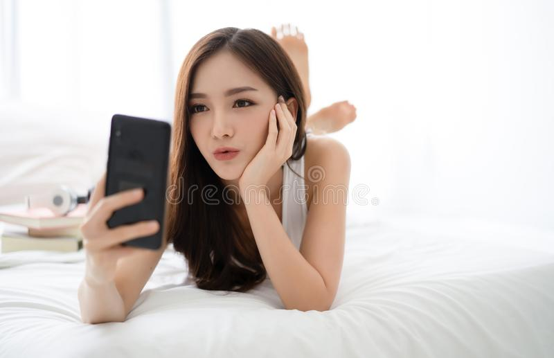 Beautiful young Asian woman making selfie using a smartphone and smiling while lying on bed. People addiction to new technology stock photography