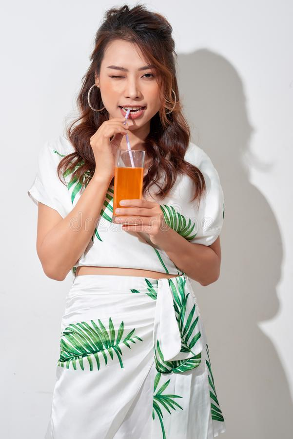 Beautiful young Asian woman with orange juice in tropical shirt on white background stock photography
