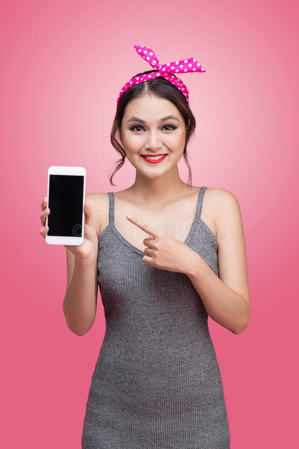 Beautiful young asian woman with pin-up make-up and hairstyle over pink background with mobile phone royalty free stock images