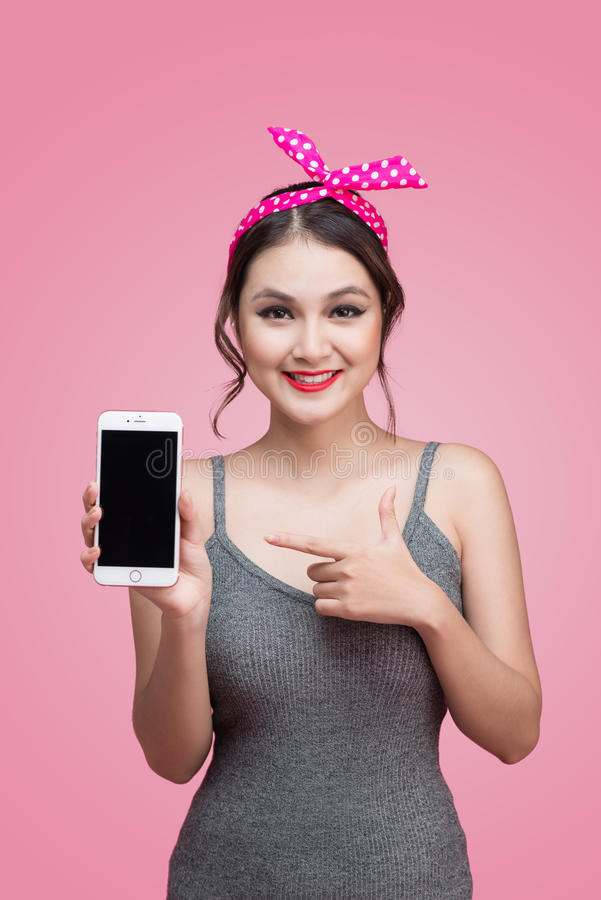 Beautiful young asian woman with pin-up make-up and hairstyle over pink background with mobile phone stock image