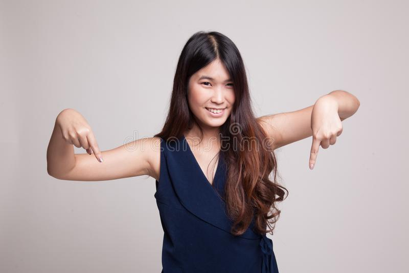 Beautiful young Asian woman point down to blank space. Beautiful young Asian woman point down to blank space on gray background stock photos
