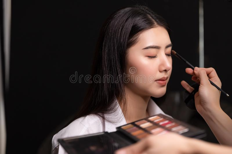 Beautiful young asian woman and professional makeup artists applies eye shadow. Beautiful woman face. Perfect makeup. royalty free stock photography