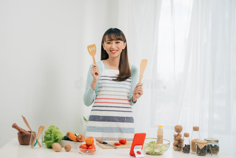 Beautiful young asian woman reading cooking recipe or watching show while making salad.  royalty free stock image