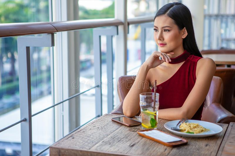 Beautiful young asian woman in red dress sitting in the restaurant looking out the window . happy elegant lady sitting on table. Thinking and waiting in date stock image