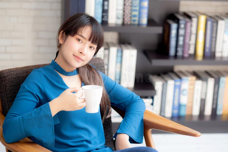 Beautiful young asian woman sitting on chair with comfort and relaxing in living room at home drinking a cup of coffee stock photo