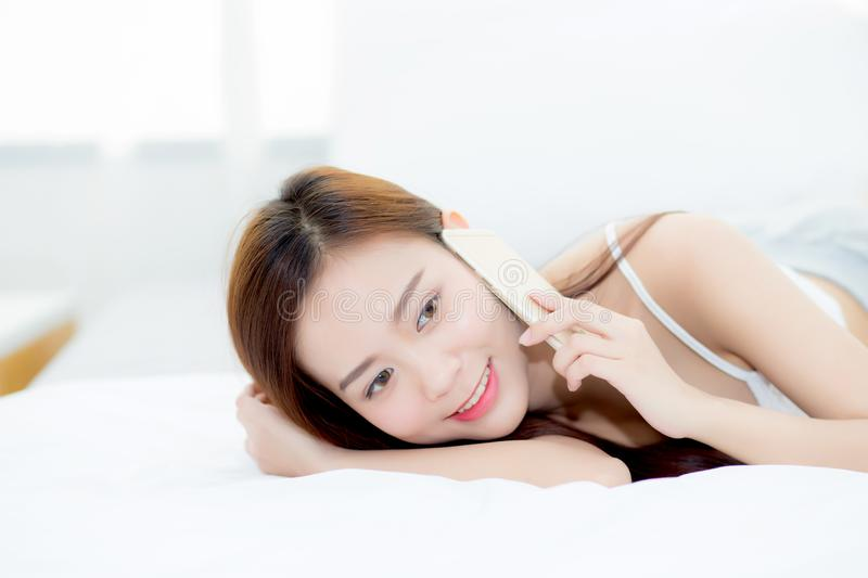 Beautiful young asian woman smiling lying and relax on the bed in the morning, girl using mobile smart phone talking enjoy stock photo