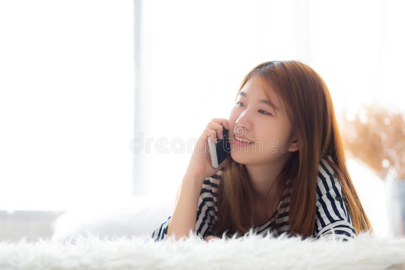 Beautiful young asian woman smiling lying relax on the bed in the morning, girl using mobile smart phone talking enjoy, royalty free stock photo