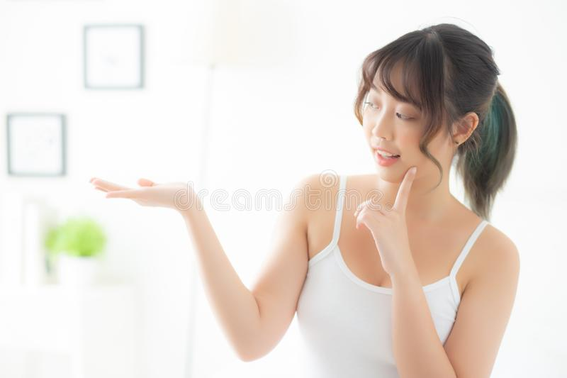 Beautiful young asian woman smiling and showing skin care product for advertisement at bedroom. Beauty asia girl presenting makeup cosmetic for advertise with royalty free stock images