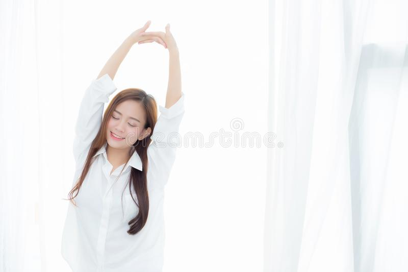 Beautiful young asian woman stretch and relax standing in bed after wake up morning at bedroom. New day and resting for wellness, lifestyle concept stock photography
