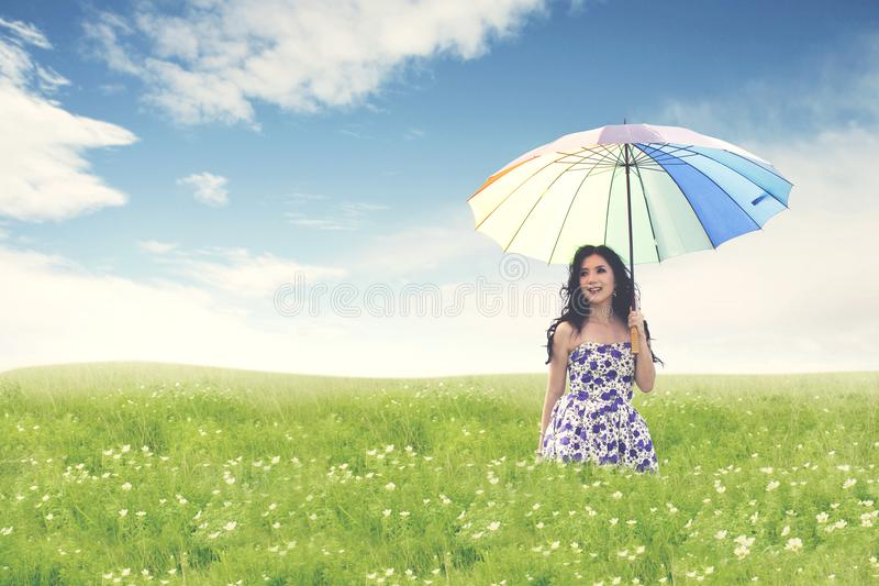 Beautiful young asian woman with umbrella on green field. Summer or spring concept royalty free stock images