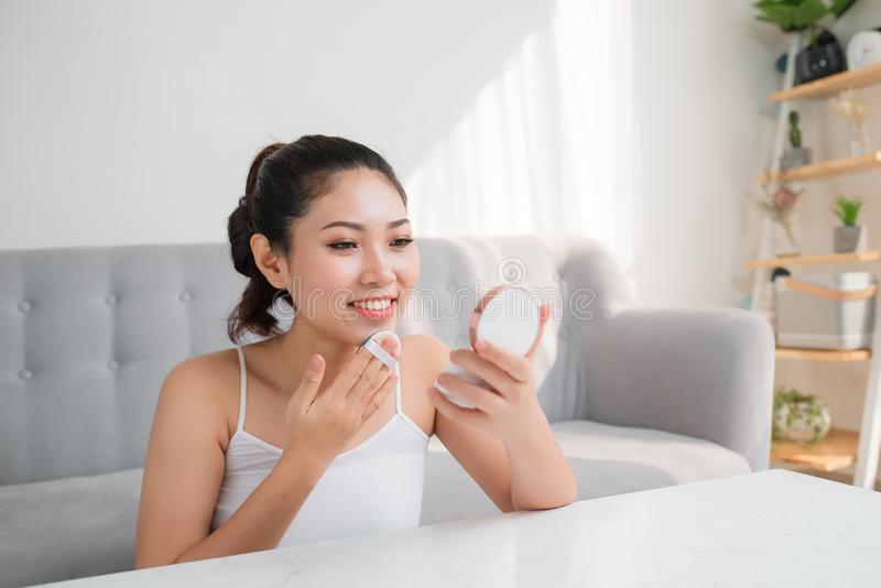 Beautiful young Asian woman using beauty blender for applying foundation for make-up on face stock photo
