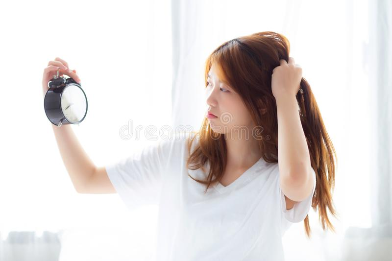 Beautiful young asian woman wake up in morning annoyed alarm clock holding hand, standing hurry wake late with appointment with c royalty free stock photo