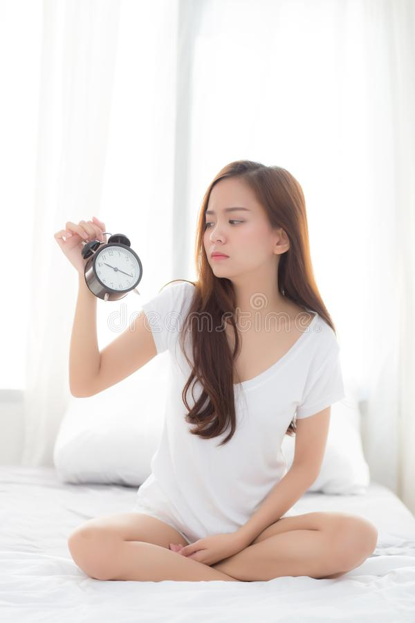 Beautiful young asian woman wake up in morning annoyed alarm clock holding hand royalty free stock images