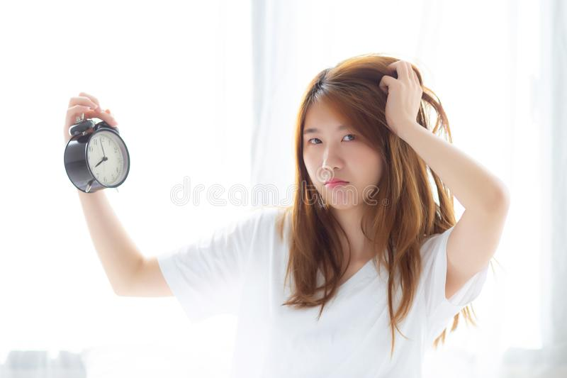 Beautiful young asian woman wake up in morning annoyed alarm clock holding hand, standing hurry wake late with appointment with c royalty free stock image