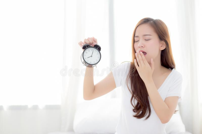 Beautiful young asian woman wake up in morning yawn and annoyed alarm clock holding hand royalty free stock photography
