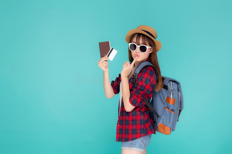 Beautiful young asian woman wear hat and sunglasses with showing credit card and passport thinking idea. In planning to travel summer trip isolated on blue royalty free stock photography