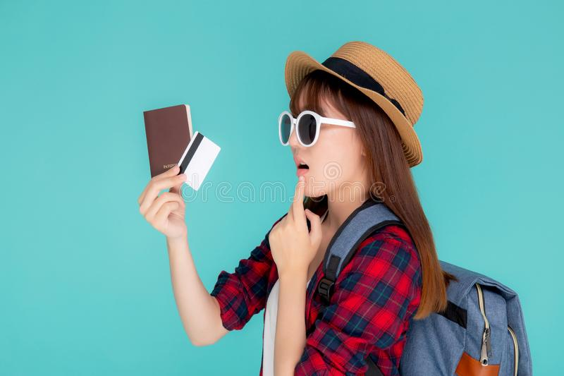Beautiful young asian woman wear hat and sunglasses with showing credit card and passport thinking idea in planning to travel. Summer trip isolated on blue stock photography