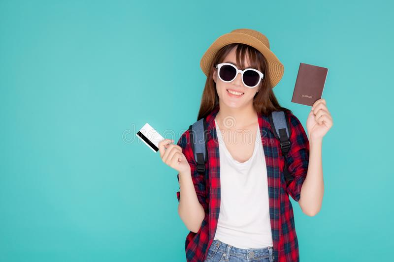 Beautiful young asian woman wear hat and sunglasses with showing credit card and passport to travel summer trip isolated. On blue background, girl journey in stock photography