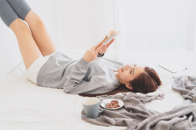 Beautiful young Asian woman wearing sweater enjoying reading a book at home lying with coffee and cookie. Concepts of home and royalty free stock image