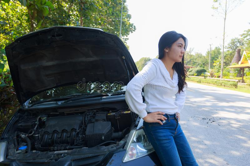 Asian woman with a broken car with open hood. Beautiful young asian woman in the white suit with a broken car with open hood royalty free stock photography