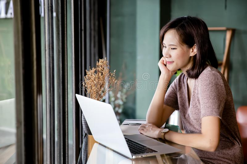 Beautiful young Asian woman working at a coffee shop with a laptop stock image