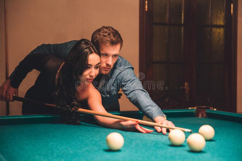 Beautiful young asian woman aiming into white billiard ball. Her boyfriend stand besides. He help her to play. They are in. Beautiful young asian women aiming royalty free stock photo