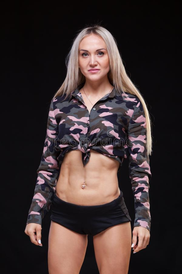 Beautiful young athletic girl with black studio background . stock photos