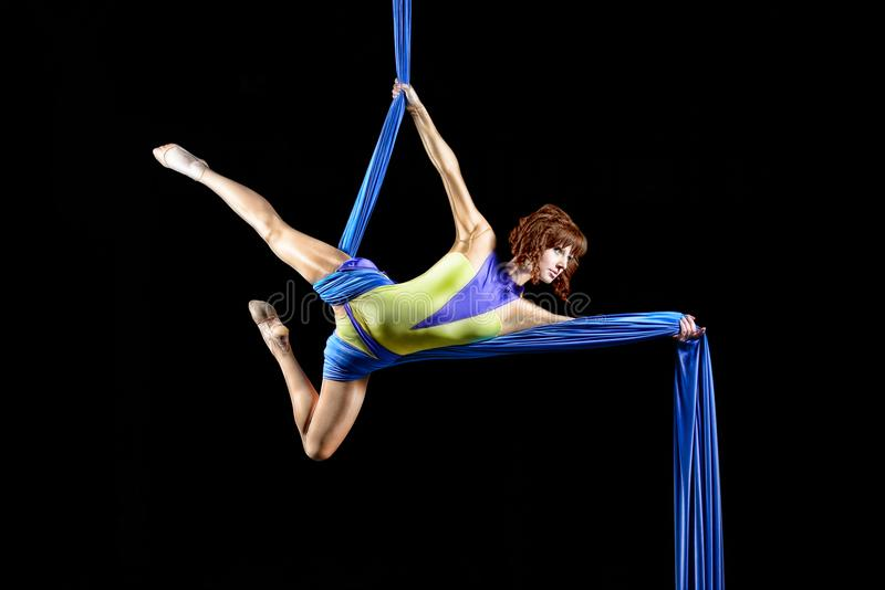 Beautiful young, athletic woman professional aerial circus artist with redhead in yellow costume posing diagonal in the air, royalty free stock image