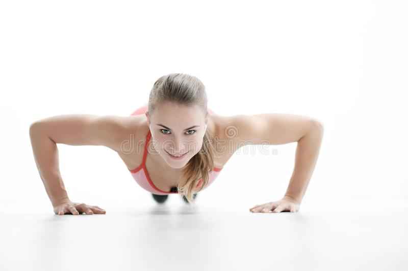 Beautiful young athletic woman blonde in sneakers and red sportswear doing push-ups on the white floor. The concept of a healthy lifestyle, fitness and sports royalty free stock photos