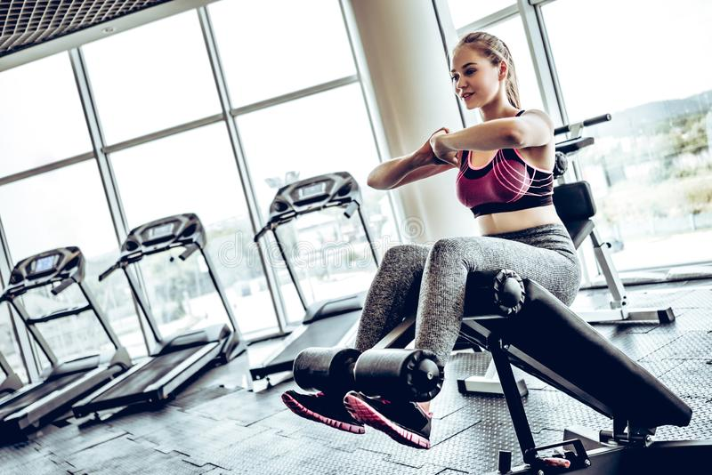 Beautiful young athletic woman doing some crunches in a bench at the gym royalty free stock photography