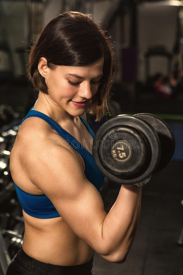 Beautiful young athletic woman exercising with dumbbells at the gym royalty free stock photography