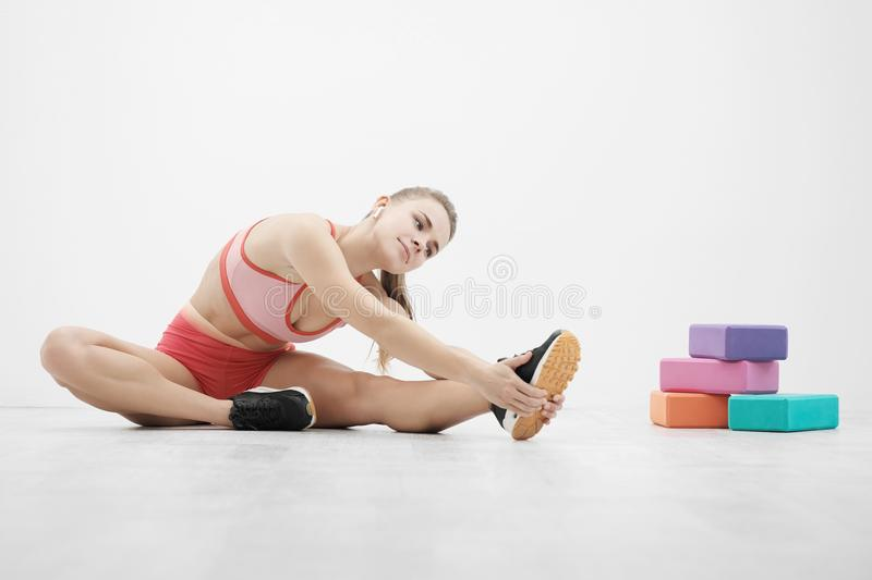 Beautiful young athletic woman in sneakers and red sportswear doing stretching on the floor. Multi-colored blocks for stock images