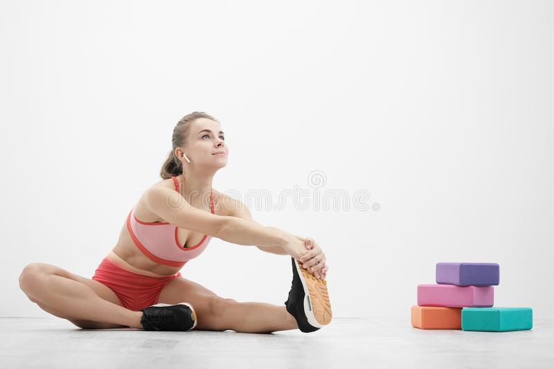 Beautiful young athletic woman in sneakers and red sportswear doing stretching on the floor. Multi-colored blocks for. Stretching and yoga. The concept of a stock photos