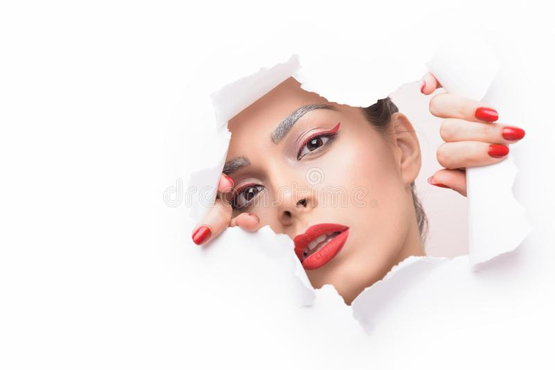 Beautiful woman looking through ripped paper. Beautiful young attractive female model with glamour makeup. Red lipstick and arrow royalty free stock photos